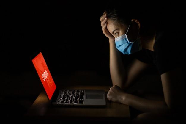 Азиатская женщина грустит и переживает из-за распространения коронавируса после проверки новостей в интернете