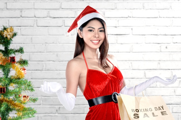Asian woman in santa costume holding shopping bags with boxing day sale text