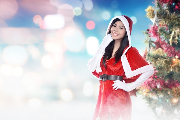 Asian woman in santa costume standing with a decorated christmas tree with colorful lights and ornaments