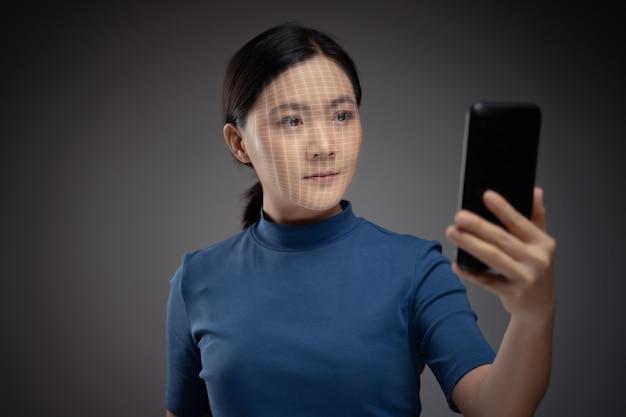 アジアの女性は、顔認識システムを使用してスマートフォンで顔をスキャンします