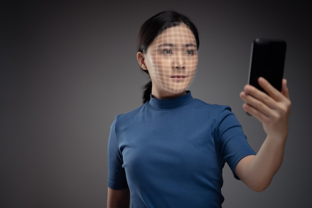 Asian woman scans face by smart phone using facial recognition system
