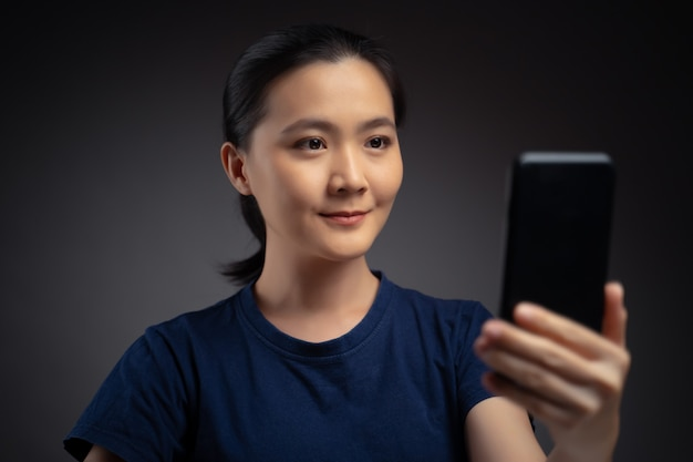 Asian woman scans face by smartphone using facial recognition system. isolated on background.