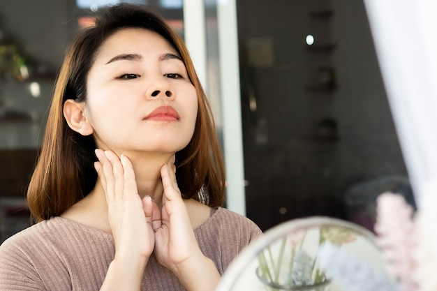 Asian woman self lymph node, checking thyroid gland on her neck