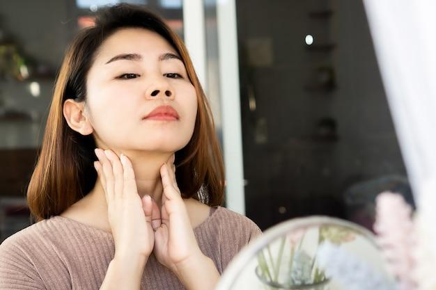 Азиатская женщина самостоятельно лимфатический узел, проверяя щитовидную железу на ее шее