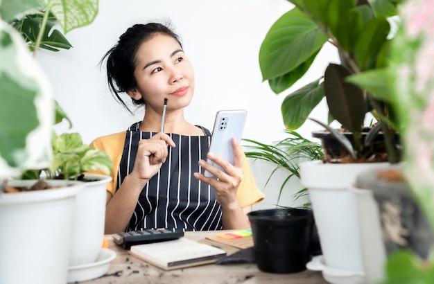 새로운 사업을 시작하기 위해 온라인으로 식물을 판매하는 아시아 여성, 휴대폰을 사용하여 집에 앉아 주문을 쓰는 성공적인 여성 가게 주인