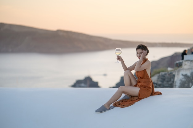 Asian woman in sexy dress witha glass of wine enjoying view oia village in santorini island, greece.