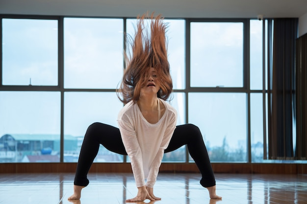 Asian woman shaking hair while dancing