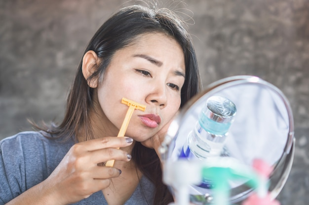 Asian woman shaving mustache on face with a razor