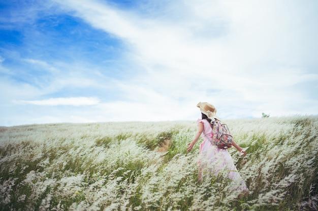 アジアの女性彼女は牧草地で自由を感じています