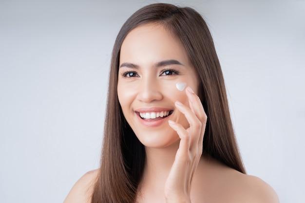 アジアの女性。彼女は顔にローションを塗っています。