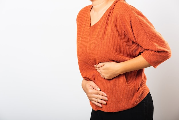 Asian woman she sick have stomach ache holds hands on abdomen part of body