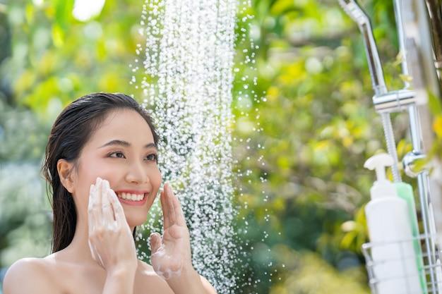 아시아 여성, 그녀는 샤워를 사용하고 외부에서 머리를 씻습니다. 그녀는 리조트에서 쉬고 있습니다.
