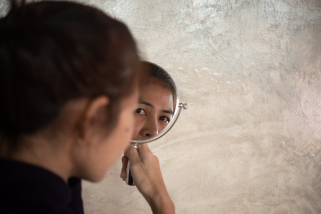 Asian woman shines in the mirror to see wrinkles and gray hair.