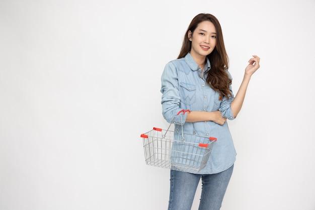 Азиатская женщина в рубашке улыбается и держит корзину для покупок, изолированные на белом фоне