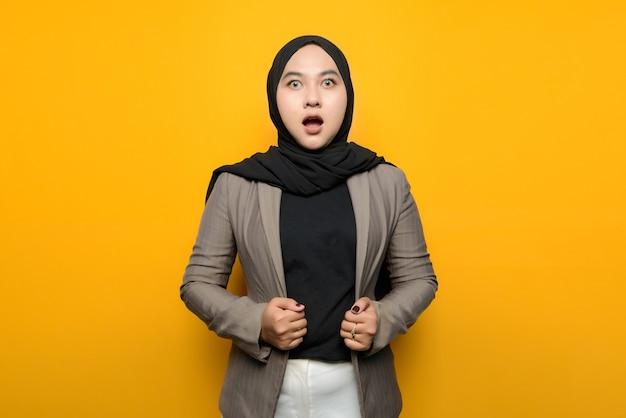 黄色の背景にショックを受けたアジアの女性