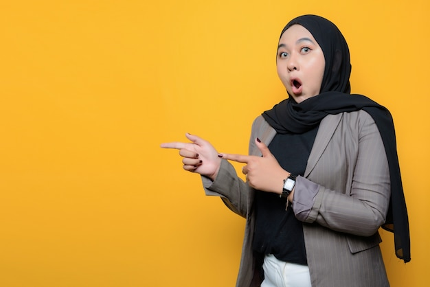 Asian woman shocked and pointing to empty space