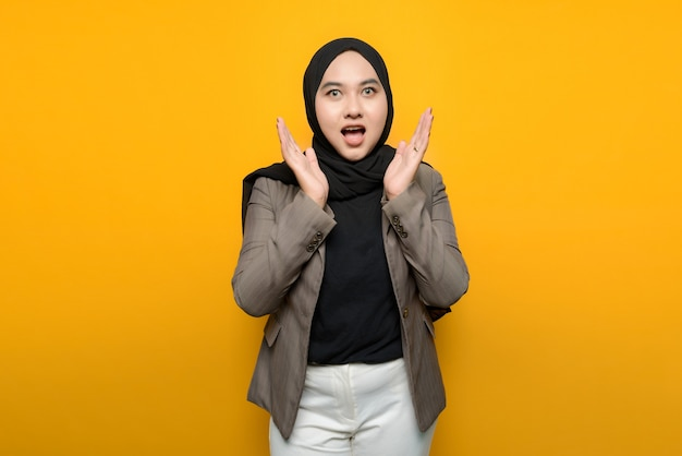 Asian woman shocked on yellow background