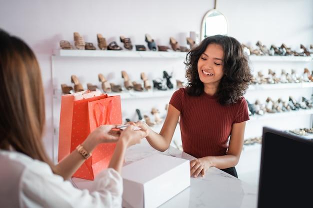 Азиатская женщина продавец с обувными коробками в магазине