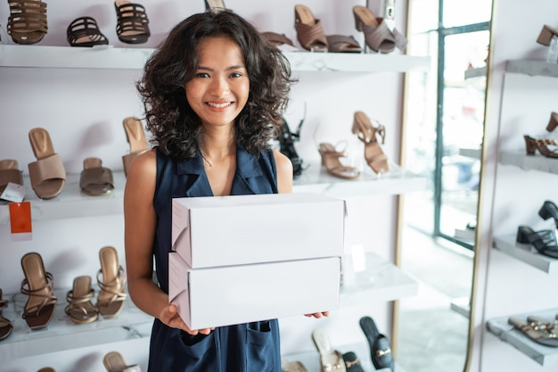 Asian woman shop assistant with shoe boxes at store