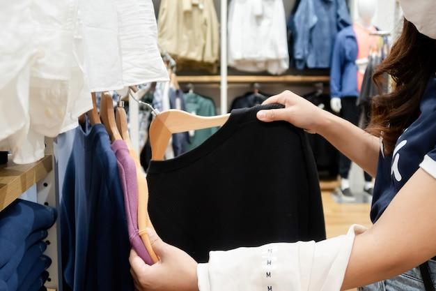 アジアの女性アジアのショッピングモールで洋服を買う。