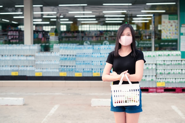 Asian woman shopping to a supermarket with a protective face mask and holding a basket