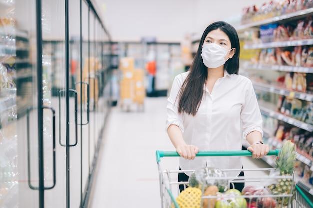 식료품, 슈퍼마켓에서 안전 조치를 위해 안전하게 구매하는 마스크로 쇼핑하는 아시아 여자.