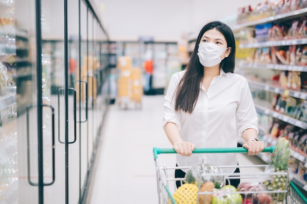 Asian woman shopping with mask safely buying for groceries , safety measures in supermarket.
