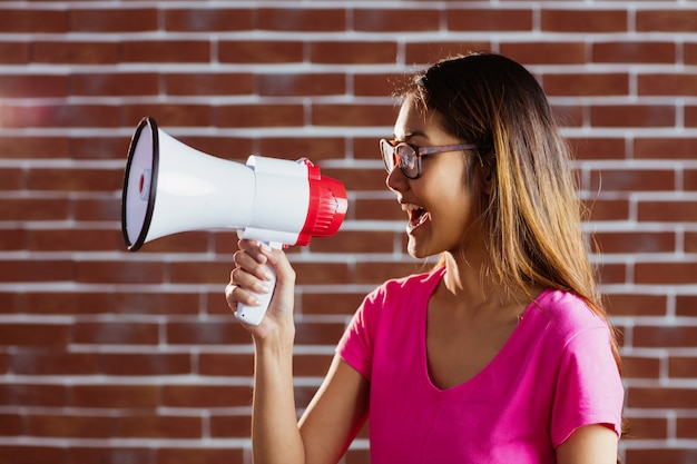 Asian woman shouting in megaphone on brick wall