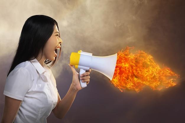 アジアの女性が火にメガホンを叫ぶ