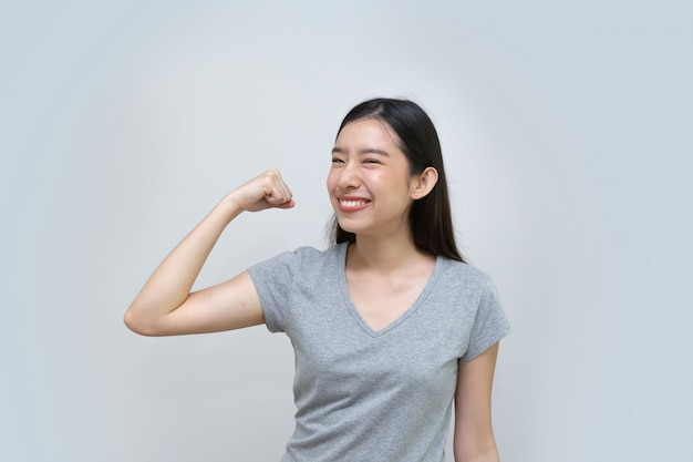 Asian woman show strong arm, beautiful young woman