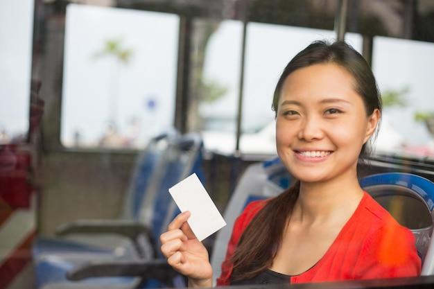 アジアの女性のショーのチケットと外に向かって笑顔