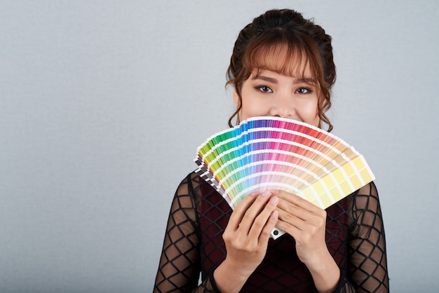 Asian woman showing colour palette covering her mouth with it