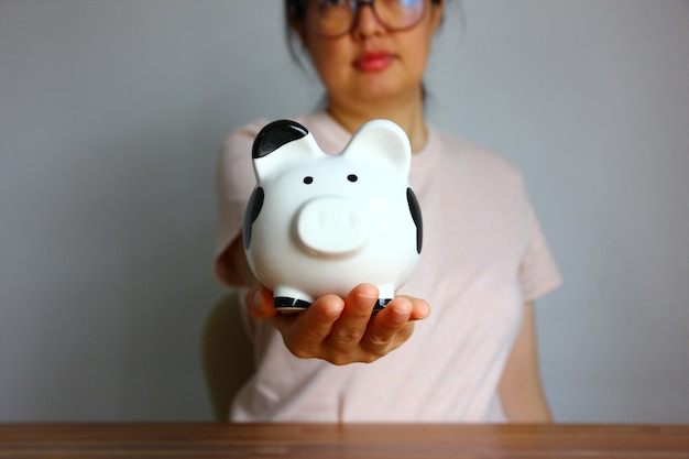 Asian woman showing her piggy bank on hand