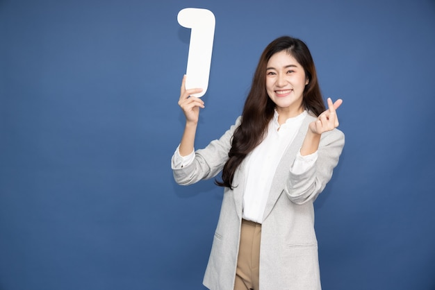 Asian woman showing number 1 and pointing up isolated on blue background