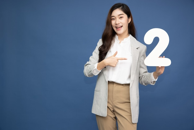 Asian woman showing number 2 and pointing up with finger isolated on blue background