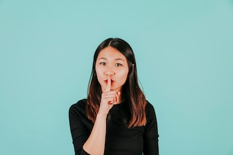 Asian woman showing silence gesture