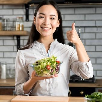 アジアの女性が台所で健康的な野菜のサラダを保持していると今すぐ登録親指を表示