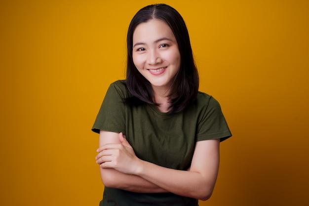노란색 벽 위에 절연 이빨 미소 서 보여주는 아시아 여자.