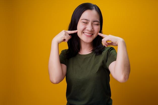 Азиатская женщина показывая зубастое положение улыбки изолированное над желтой стеной.