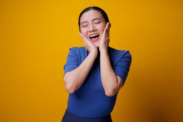 노란색 위에 이빨 미소 서 보여주는 아시아 여자.
