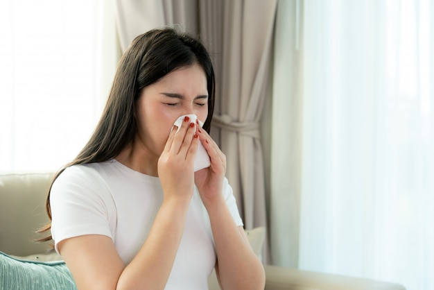 Asian woman sick and sad with sneezing on nose and cold cough on tissue paper