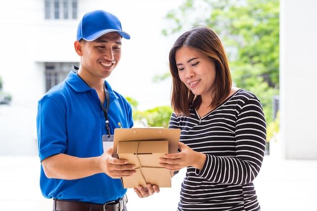 配達されたパッケージの受領書に署名するアジアの女性