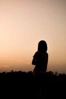 Asian woman silhouette over sunset