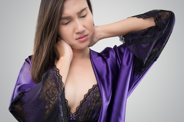 Asian woman in the silk nightwear and purple robe who is having pain in her neck on a gray background