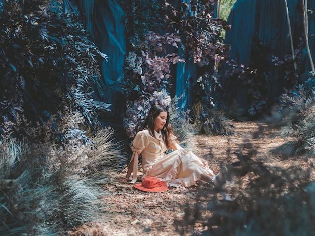 アジアの女性は、青い洞窟のファンタジー色の森に座って考えています