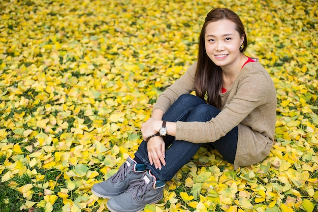 Asian woman sit on ginkgo leaves background in the garden.
