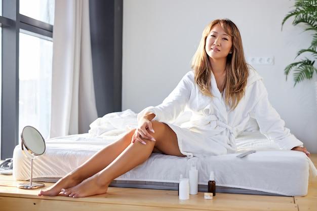 アジアの女性は、滑らかな脚の肌に触れるバスローブでベッドに座って、化粧品を使用して、寝室で美容手順を楽しんでいます