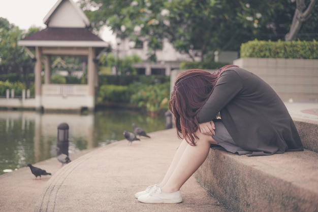Asian woman sitting alone and depressed, portrait of tired young woman. depression