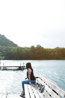 Asian woman sitting alone on wooden bench near lake.