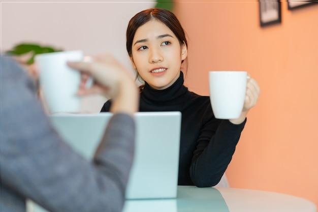 퇴근 후 커피숍에서 동료들과 앉아서 이야기를 나누는 아시아 여성